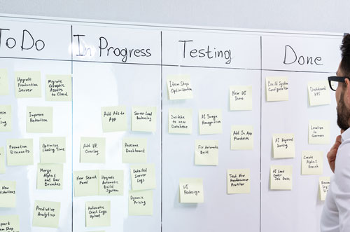 man-standing-at-kanban-board-managing an IT project with Agile methodology
